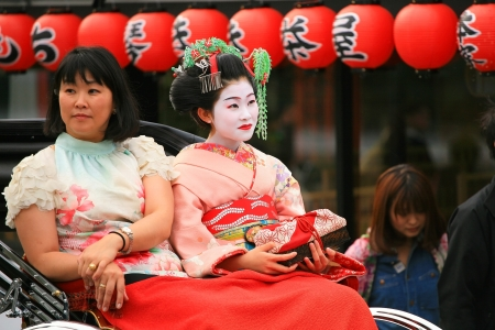 blossom time: ARASHIYAMA-APR 17  Unidentified girl on rickshaw dresses traditional japanese Kimono to enjoy cherry blossom on April 17, 2011 in Arashiyama, Japan  Arashiyama is famous on sakura blossom time