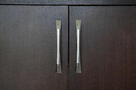 grasp: Closeup wooden black cabinet with metal grasp