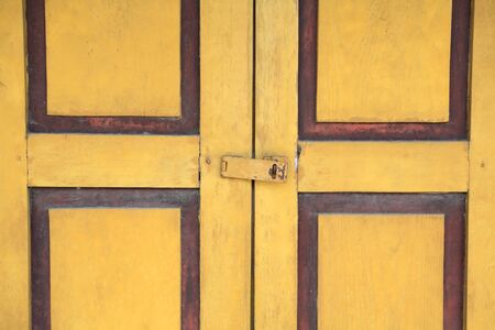 Closeup yellow door with old metal lock  photo