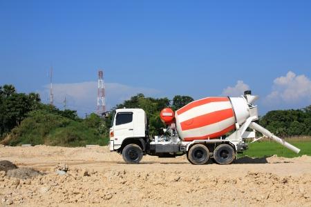 Heavy concrete truck on construction site against blue sky