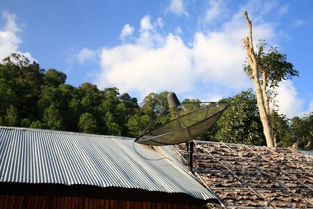 Black satellite dish on zinc and old wood roof in suburb photo