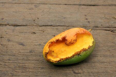 rotten ripe mango bitten by insects on wooden board photo