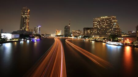 BANGKOK-DEC 05  Cityscape of boat light trails on Chao Phraya River in Bangkok, Thailand on December 05, 2012  Boat can transfer to historic, business, and resident spots around Bangkok by 9 piers   Stock Photo - 16782150