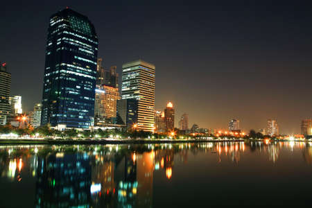 Bangkok cityscape of modern tower buildings with skyline reflection at Benjakitti park photo