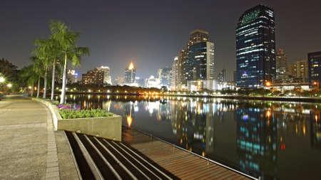 Bangkok city view at night with skyline reflection at Benjakiiti park photo