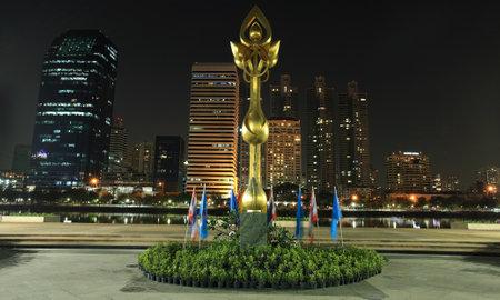 Golden lotus statue against modern buildings at Benjakitti park in Bangkok