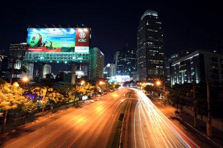 reign: BANGKOK-JAN 18 Light trails on Ratchadaphisek street to Asoke junction on January 18,2013 in Bangkok,Thailand  Ratchadaphisek steet is established on 1971 to celebrate 25th reign of King Bhumibol   Editorial