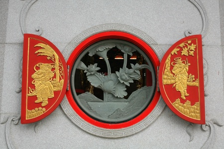 Open red wood window decorated with gold chinese style sculpture photo