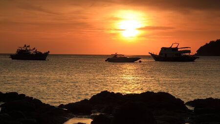 Tropical sunset scene while ferry and boats floating on Andaman sea at Koh Lipe island in Thailand photo