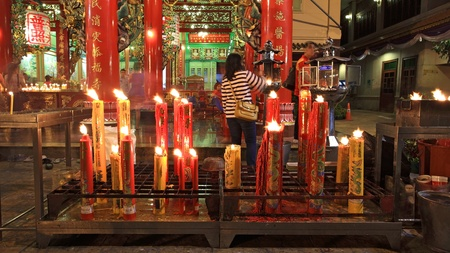venerate: BANGKOK-FEB 09  Unidentified people incense near big candles to pray in Chinese new year day at Kuan Yin shrine on Febuary 09, 2013 in Bangkok, Thailand  Here is located near China town Gateway Arch  Editorial
