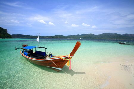 longtail: Long tail boat on white sand beach and crystal turquoise sea at Lipe island, Thailand