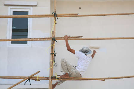 Worker on wooden scaffold painting wall of construction building  photo