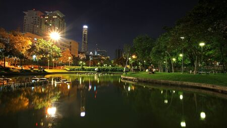 Santiphap Park at twilight with skyline reflection on the pond near victory monument in Bangkok, Thailand photo