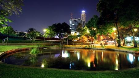 Santipap Park with skyline reflection on the pond at dusk in Bangkok, Thailand photo