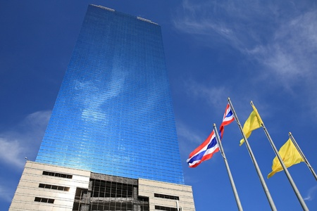 Modern glass commercial office building against blue sky with thai flag