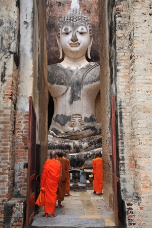 Thai monks worship large Buddha statue at Wat Sri Chum in Sukhothai, Thailand