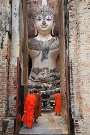 Thai monks worship large Buddha statue at Wat Sri Chum in Sukhothai, Thailand