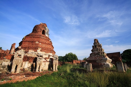Ruin Lion statues and pagoda against blue sky at wat Thammikarat in  in Ayutthaya, Thailand   photo