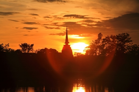 Silhouette scene of pagoda at sunset with flare sunlight in Sukhothai historical park, Thailand photo