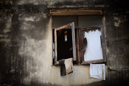 Broke wooden windows with hanging cloths at grunge wall