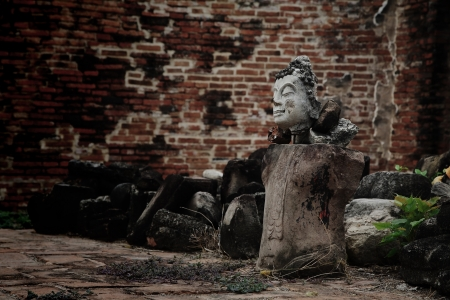 without legs: Ruin Buddha statue without legs and hands with grunge brick wall