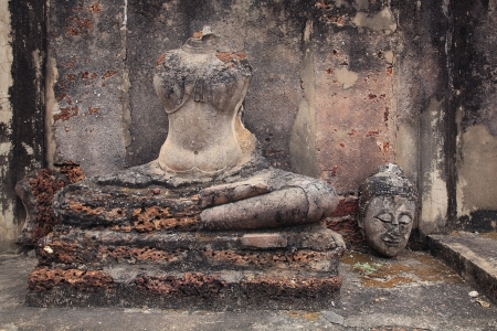 Ruin sitting Buddha statue with the head beside statue at Wat Phra Sri Rattana Mahathat in Si Satchanalai historical park of Sukhothai, Thailand  photo