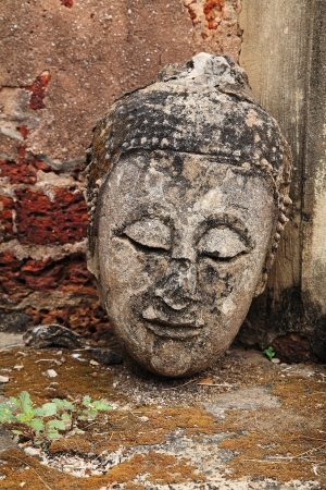 Ancient Buddha head without body at Srisatchanalai historical park in Sukhothai, Thailand  photo