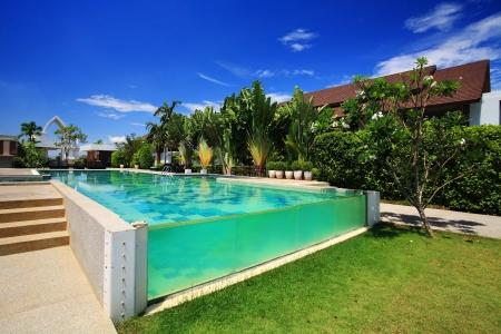 Luxury resort swimming pool against blue sky