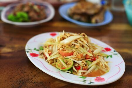 SomTum, Thai Green Papaya Salad on wooden table photo