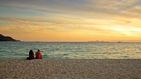 Couple sitting on the beach to enjoy sunrise at Koh Lipe, Satun, Thailand photo