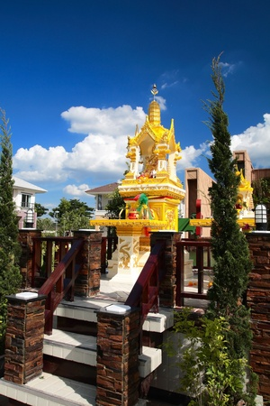 Gold joss house against blue sky in Thailand photo