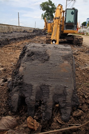 scoop shovel of yellow excavator machine diging dirt photo