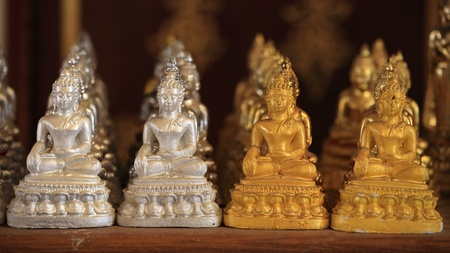Many gold and silver small Buddha statues photo