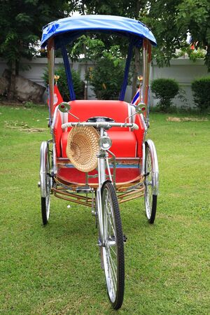 peddle: Thai Rickshaw or tricycle parking on the grass to show