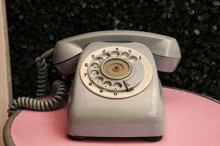 oldened: Vintage analog telephone on pink table