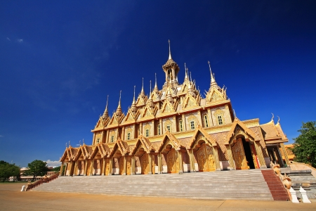 Golden pagoda against blue sky at Wat Tha Sung in Uthai Thani, Thailand photo