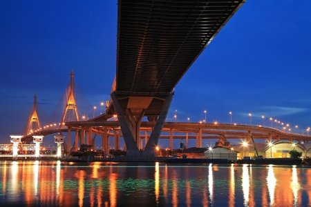 Bhumibol Suspension, aka Industrial Ring Road, Bridge across Chao Phraya river with light trail at twilight in Bangkok, Thailand photo
