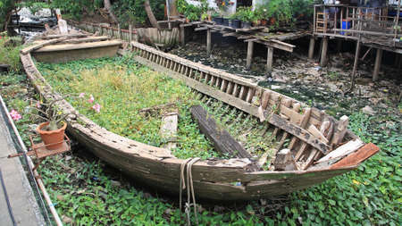 skiff: Rotted and abandoned row wooden boat at Thai village