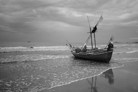 lovelorn: Black and white  Stranded fisherman boat on the beach with wave