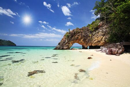 Natural stone arch against sunbeam and tropical andaman sea at Kho Khai in Satun, Thailand photo
