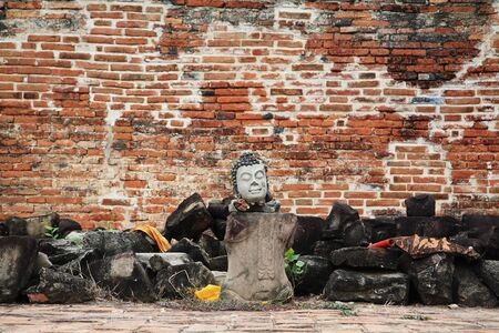 rule of thirds: Buddha statue without arms and legs in front of grunge wall in Ayutthaya, Thailand Stock Photo