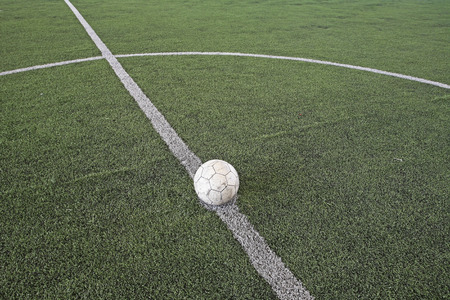 Soccer ball at kickoff spot on fake soccer field photo