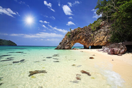 Natural stone arch against sunbeam at Kho Khai near Tarutao national park and Koh Lipe in Satun, Thailand photo