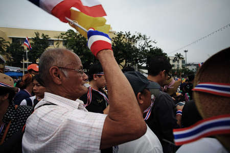 amnesty: BANGKOK-NOV 24:  Unidentified old anti-government man blows whistle and raise Thai flag to make symbolic protest against the amnesty bill on Nov 24, 2013 in Bangkok, Thailand. It claims that up to million Thai people gather on such day.
