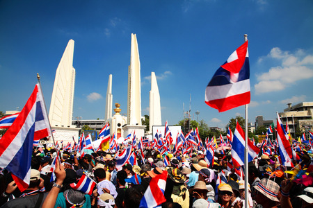 BANGKOK-DEC 1: protesters raise Thai flags at Democracy Monument to anti government amnesty bill on December 01, 2013 in Bangkok, Thailand. Protesters rally to majority government ministries today.