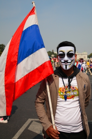 guy fawkes mask: BANGKOK-DEC 9: Unidentified Thai protester wearing  Guy Fawkes mask with Thai flag on December 09, 2013 in Bangkok, Thailand. Millions of Thai people rally from many streets to expel government today.