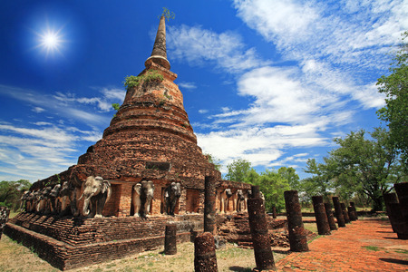 Elephant statues around ancient pagoda against blue sky and sunbeam at Wat Chang Lom in Sukhothai, Thailand photo