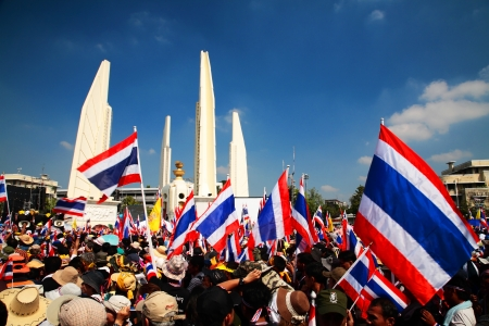 amnesty: BANGKOK-DEC 1  protesters raise Thai flags at Democracy Monument to anti government amnesty bill on December 01, 2013 in Bangkok, Thailand  Protesters march to majority government ministries today