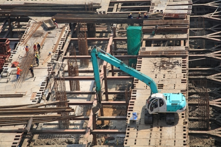 Crane and workers at construction site by aerial view