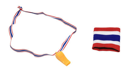 Thai flag wristband and yellow whistle isolated on white photo